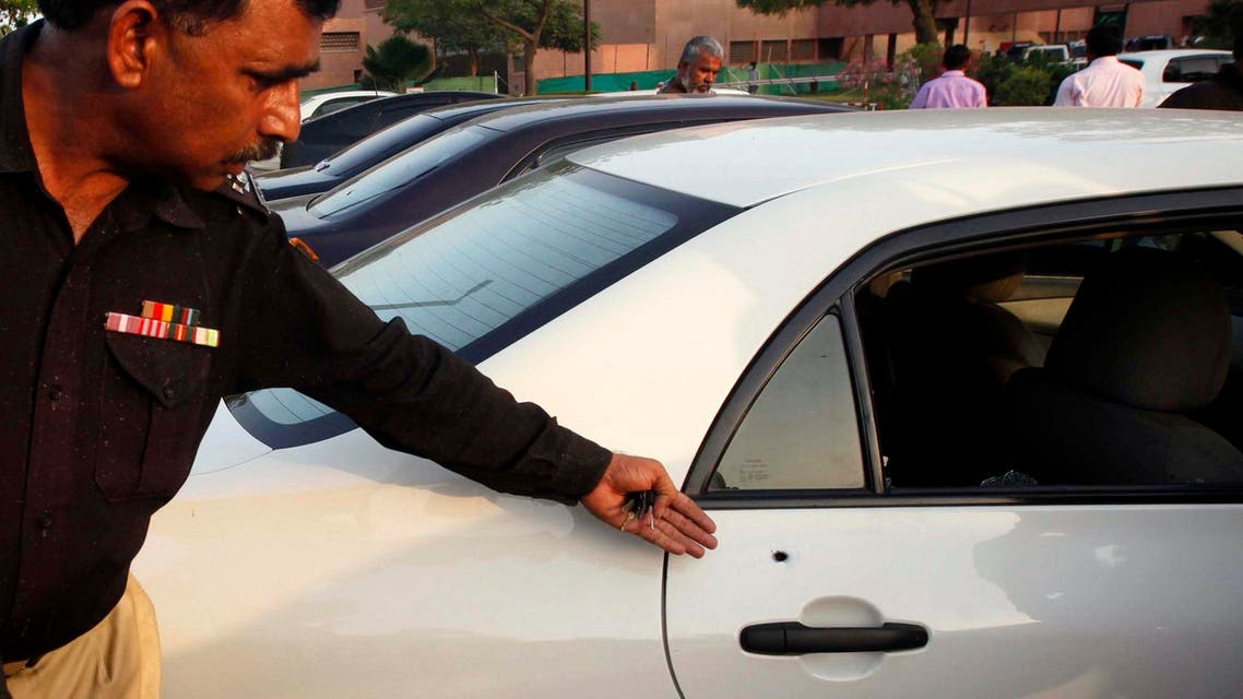 A policeman shows a bullet hole in a car belonging to journalist Hamid Mir. Unknown gunmen on motorcycles opened fire and injured Mir in Karachi on Saturday. (Reuters)