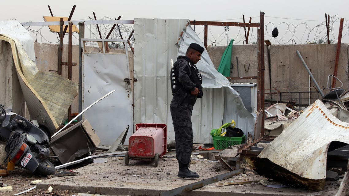 An Iraqi policeman inspects the site of a suicide bombing at the university of Imam Kadhim University in the capital Baghdad on April 20, 2014. (AFP)