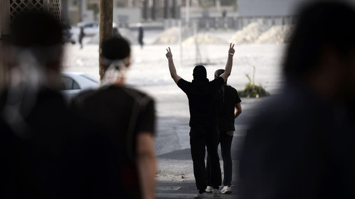 A Bahraini protester flashes the sign of victory in front of riot police. (AFP)