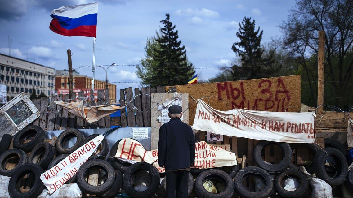 An elderly man stands next a barricade near the secret service building in the eastern Ukrainian city of Lugansk on April 22, 2014. afp