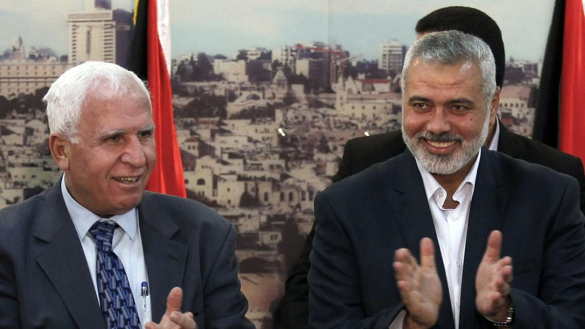Palestinian Fatah delegation chief Azzam al-Ahmed (L) celebrates with Hamas prime minister in the Gaza Strip Ismail Haniya in Gaza City on April 23, 2014. (AFP)