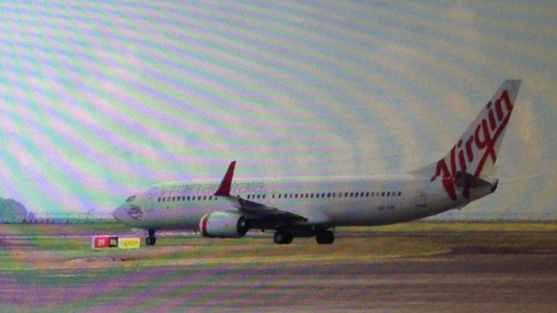 This photo taken through the window of a plane shows a Virgin Australia plane at the centre of a hijacking scare sitting on the tarmac at Bali airport in Denpasar on April 25, 2014.  (AFP)