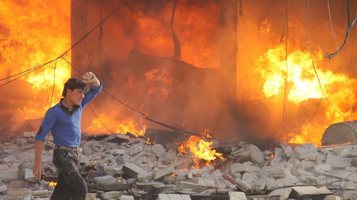 A man walks past a burning building following a reported air strike by pro-regime forces on the northern Syrian city of Aleppo, on April 24, 2014. (AFP)