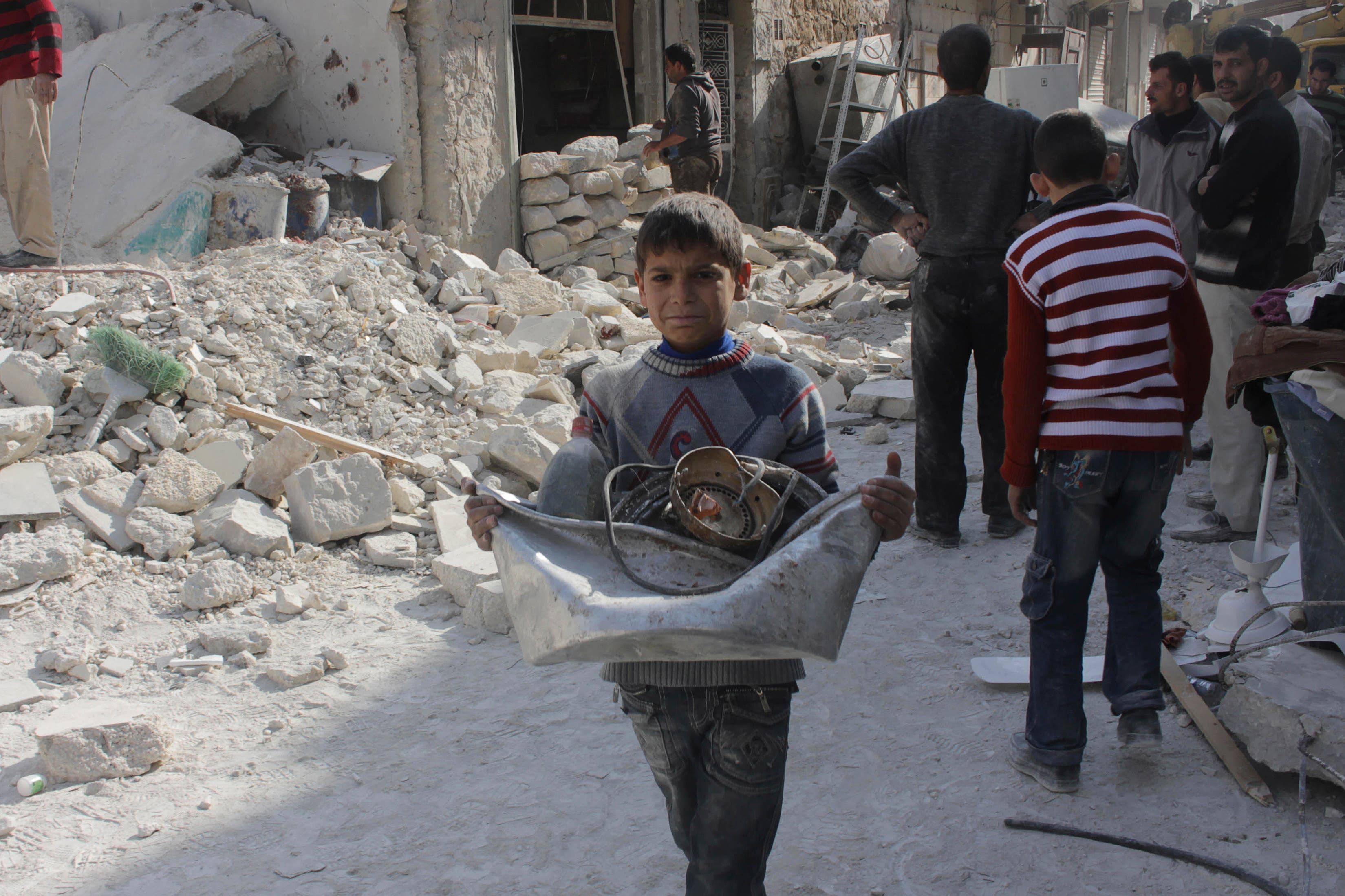 A boy collects his belongings amidst the rubble of collapsed buildings after what activists said was shelling by forces loyal to Syria's President Bashar al-Assad in Aleppo. (File photo: Reuters)