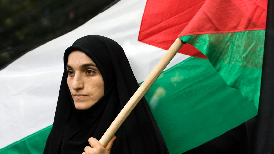 A woman holds a Palestinian flag outside the United Nations headquarters building in Tehran REUTERS