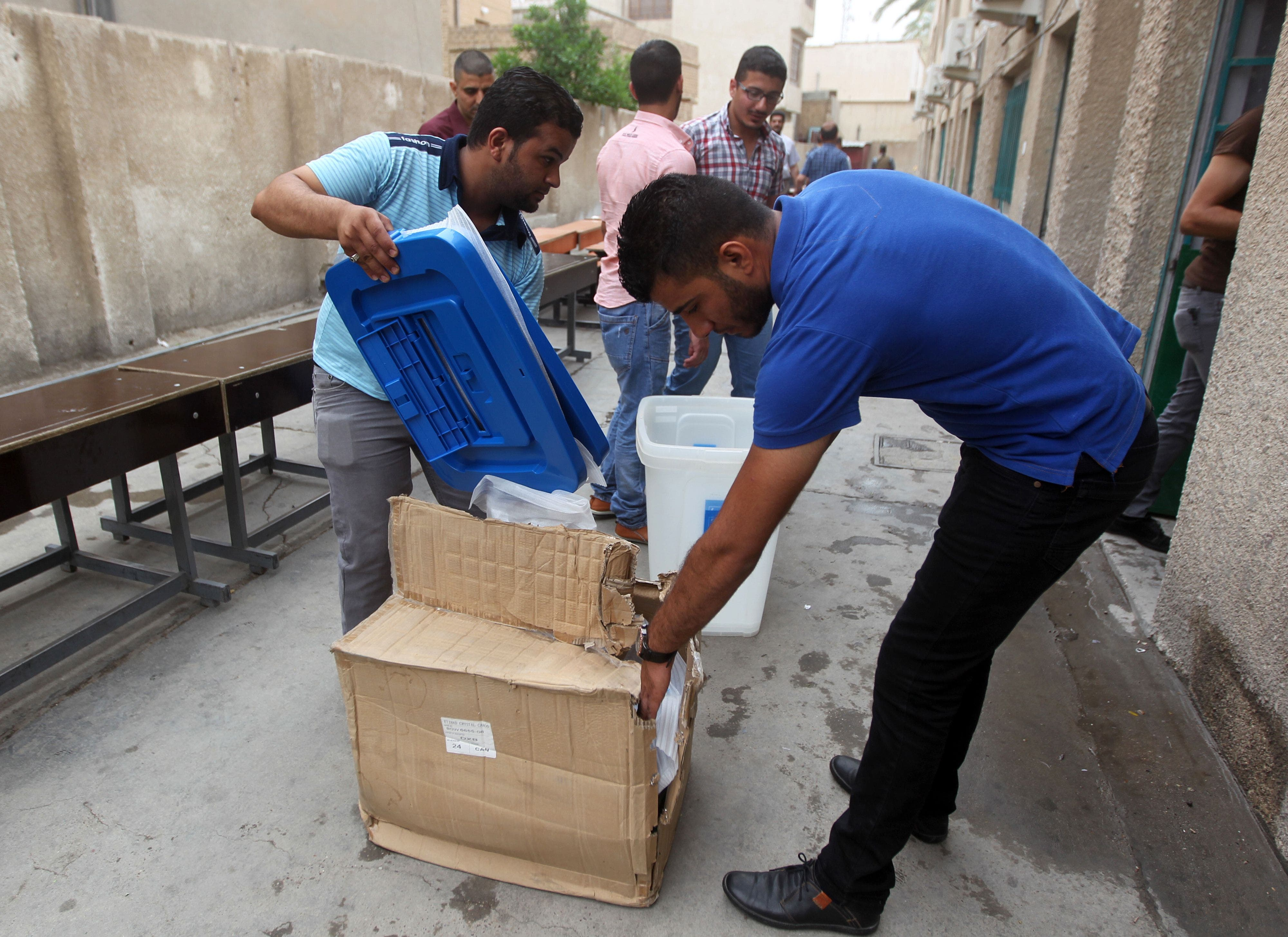 Employees distribute election material during vote preparations at a polling station on April 27, 2014 in the capital Baghdad ahead of the upcoming parliamentary elections in Iraq. (AFP)