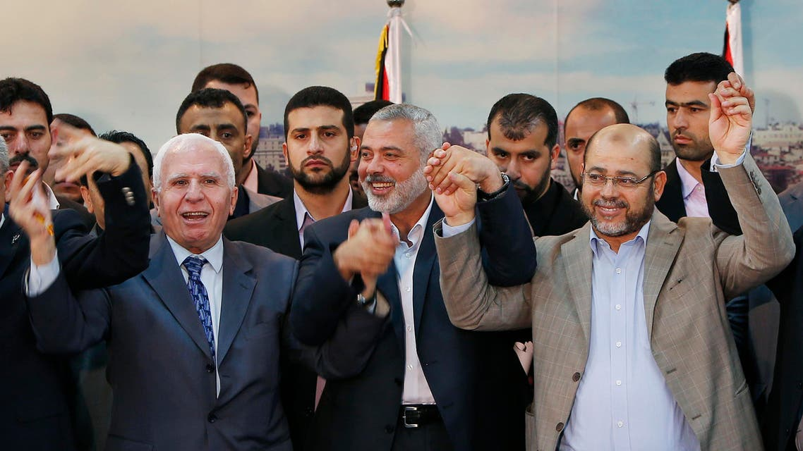 Senior Fatah official Azzam Al-Ahmed (L), head of the Hamas government Ismail Haniyeh (C) and senior Hamas leader Moussa Abu Marzouq hold their hands after announcing a reconciliation agreement in Gaza City April 23, 2014