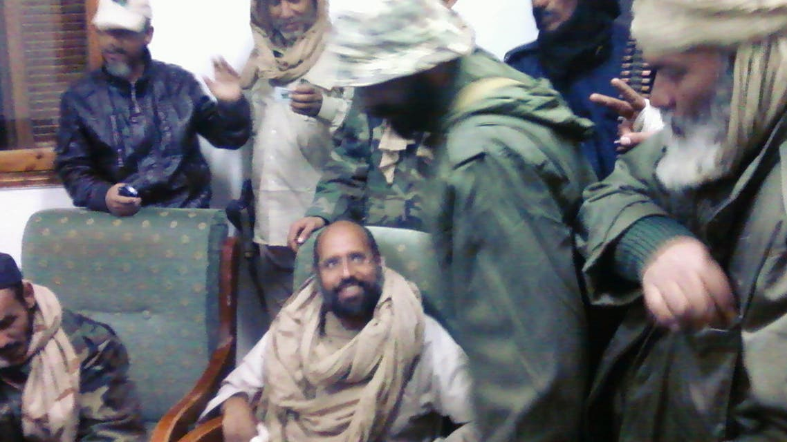 A mobile phone picture taken by one of his guards shows Saif al-Islam Gaddafi sitting with his captors in Obari airport November 19, 2011. (File photo Reuters)