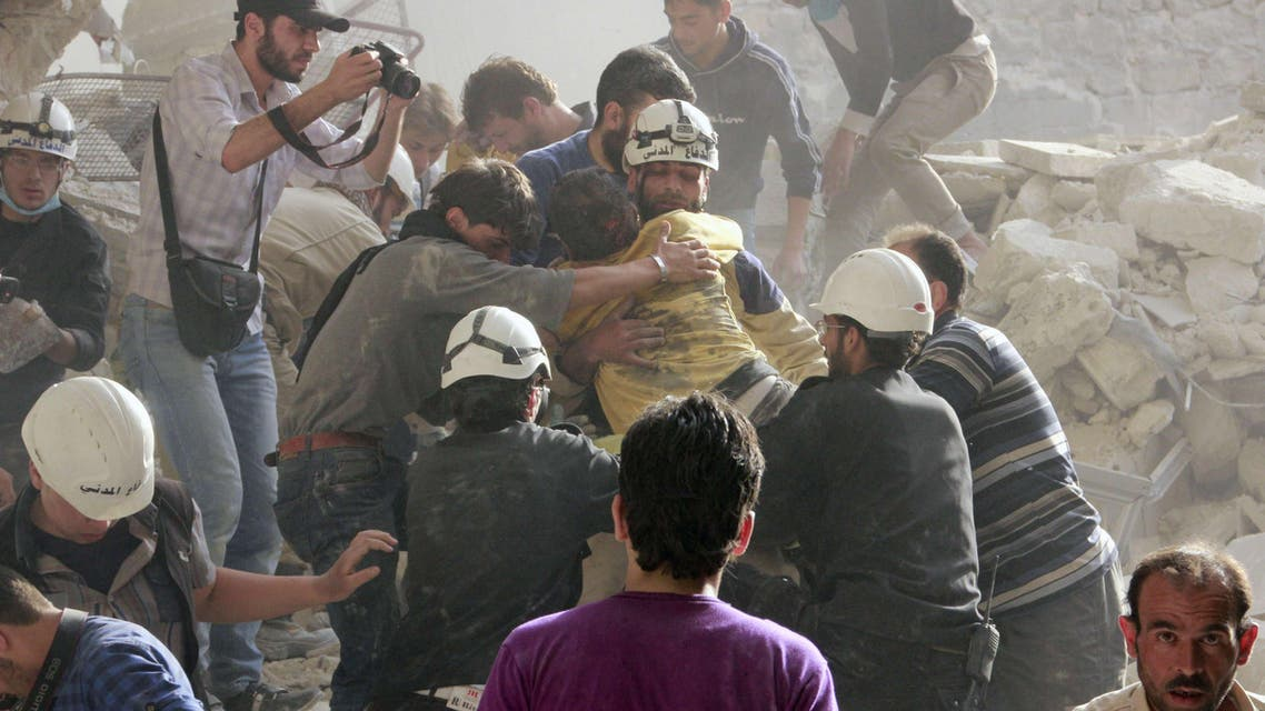 Emergency responders rescue a man that was buried under rubble after a building collapsed following a reported barrel-bomb attack on the northern Syrian city of Aleppo, on April 25, 2014. AFP