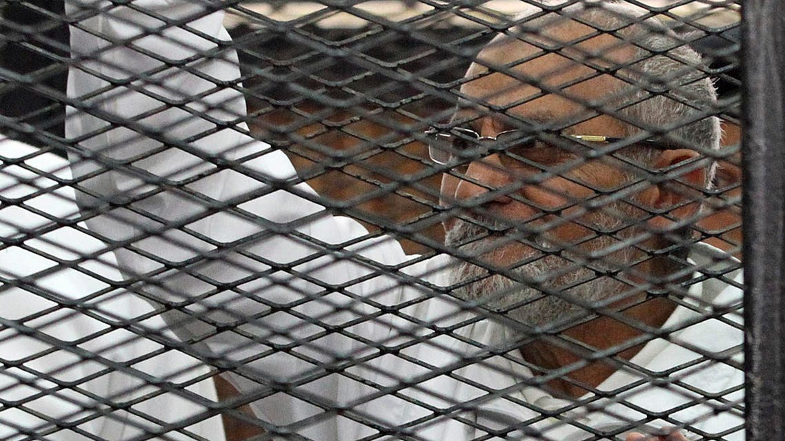 Muslim Brotherhood leader Mohammed Badie looks on from the defendant's cage during his trial with other leaders of the group in a courtroom in Cairo December 11, 2013. P