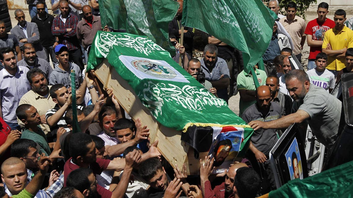 Palestinian mourners wave the green flag of the Islamist movement Hamas as they attend the funeral of two Hamas members who were killed in 1998, Adel and Imad Awadallah, in the West Bank city of Ramallah on April 30, 2014. (AFP)