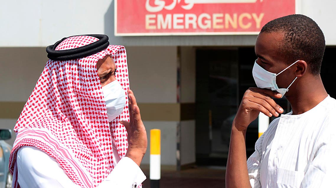 Men wearing surgical masks as a precautionary measure against the novel coronavirus, speak at a hospital in Khobar city in Dammam May 23, 2013. (Reuters)