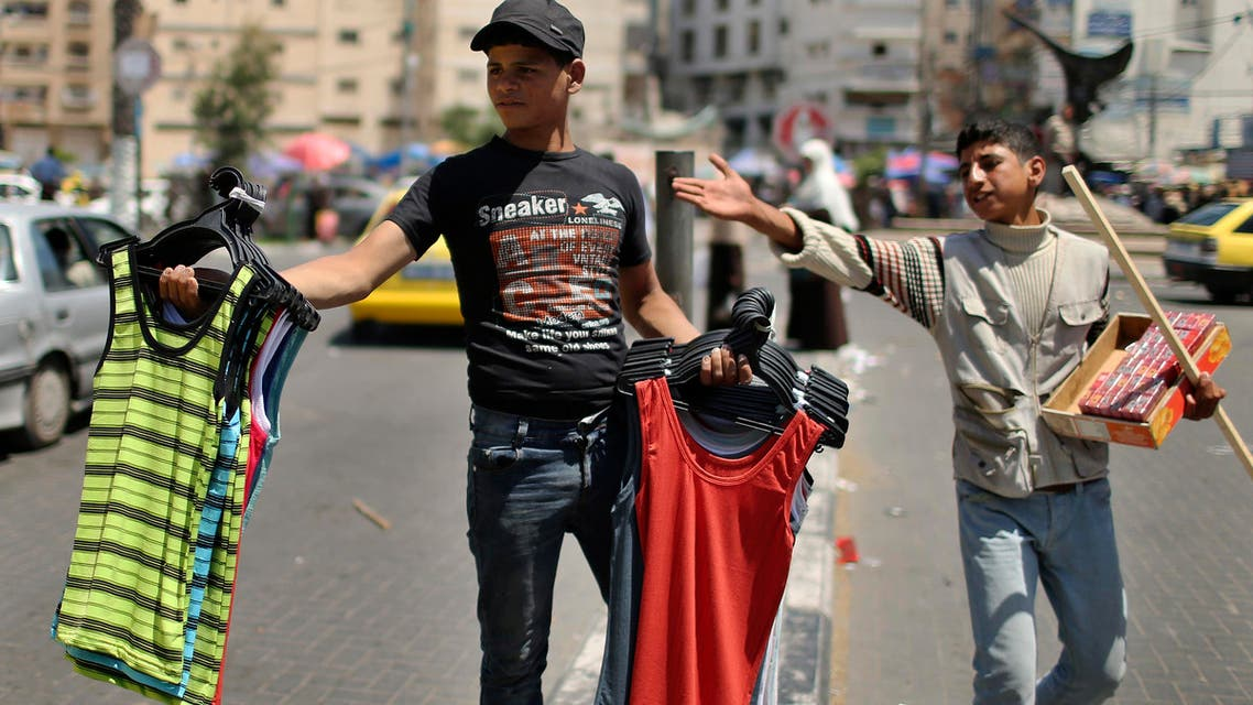 Palestinian boys sell cigarettes and clothes on a street in Gaza City May 1, 2014. (Reuters)