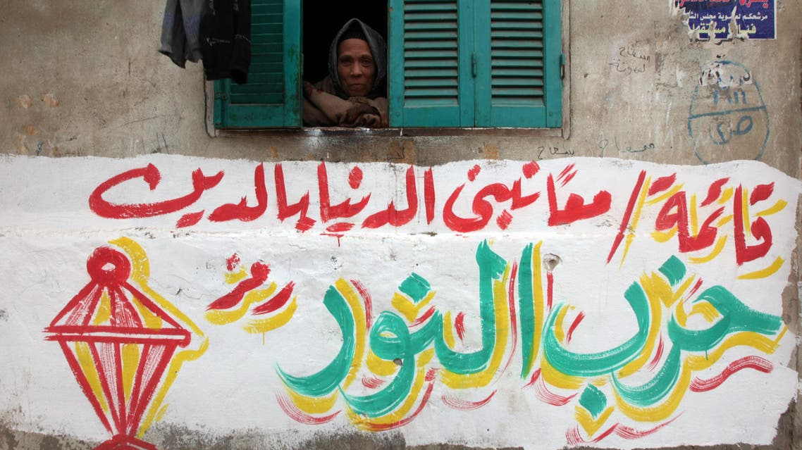 """A woman looks through her window above an electoral slogan for Salafi political party Al-Nour that reads, """"Together hand in hand we build the country through religion."""" Reuters"""
