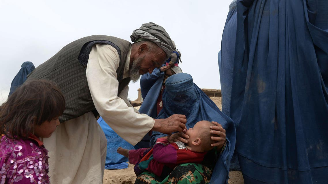 A landslide-affected child receives polio vaccination drops during aid distribution at the scene of the disaster in Argo district of Badakhshan on May 4, 2014. (AFP)