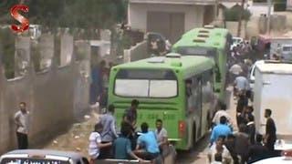 حافلات تقل المسلحين اثناء خروجهم من حمص باتفاق الهدنة