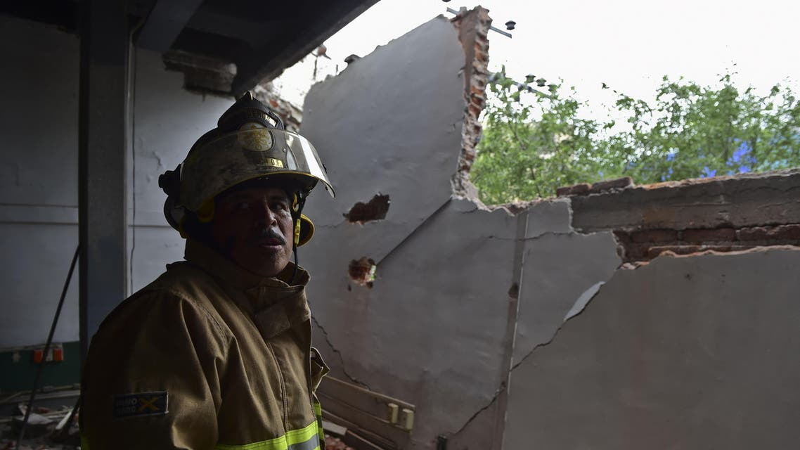A firefighter works to demolish a damaged wall after a strong earthquake in Mexico City on May 8, 2014. (AFP)