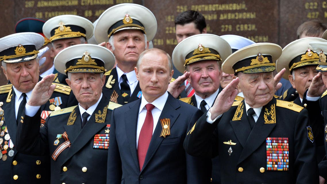 Russia's President Vladimir Putin (C) and World War II veterans watch a parade of honor guard during his visit to the Crimean port of Sevastopol on May 9, 2014. (AFP)