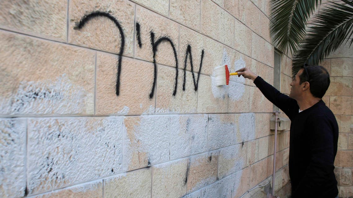 A municipality worker paints over graffiti daubed in Hebrew on a wall of the Romanian Orthodox Church in Jerusalem May 9, 2014.  (Reuters)