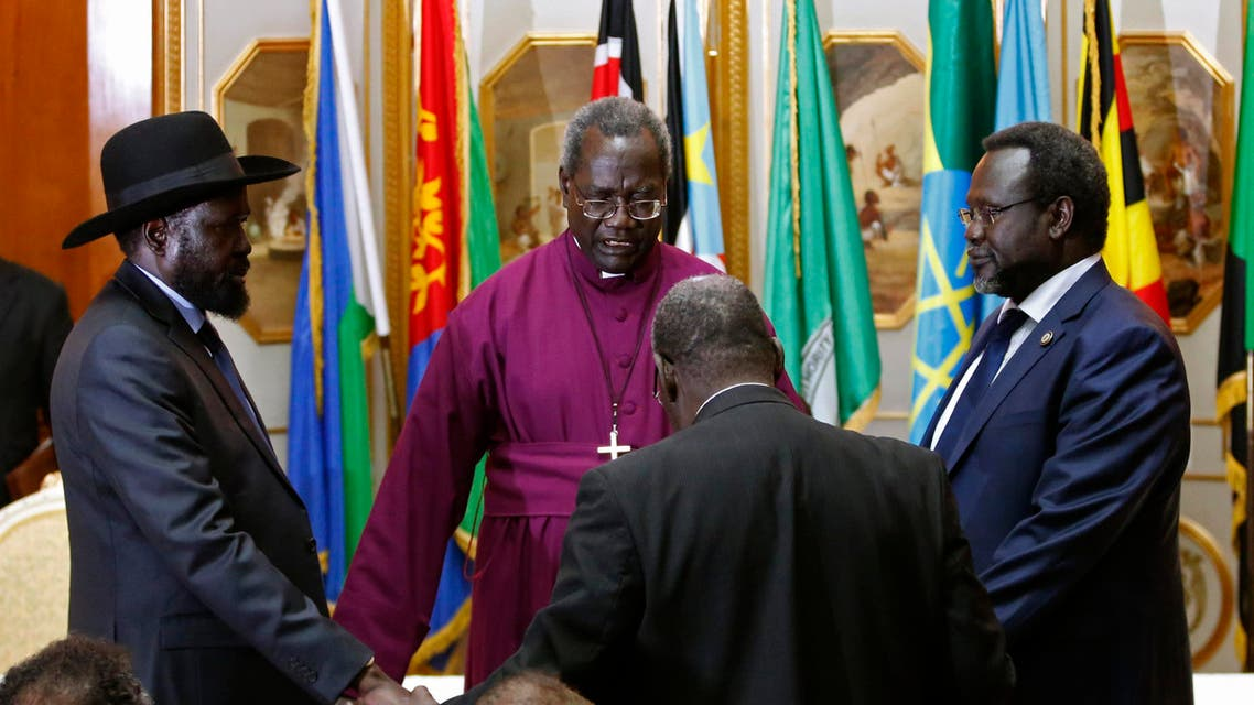 South Sudan's rebel leader Riek Machar (R) and South Sudan's President Salva Kiir (L) hold a priest's hands as they pray before signing a peace agreement in Addis Ababa May 9, 2014.  reuters