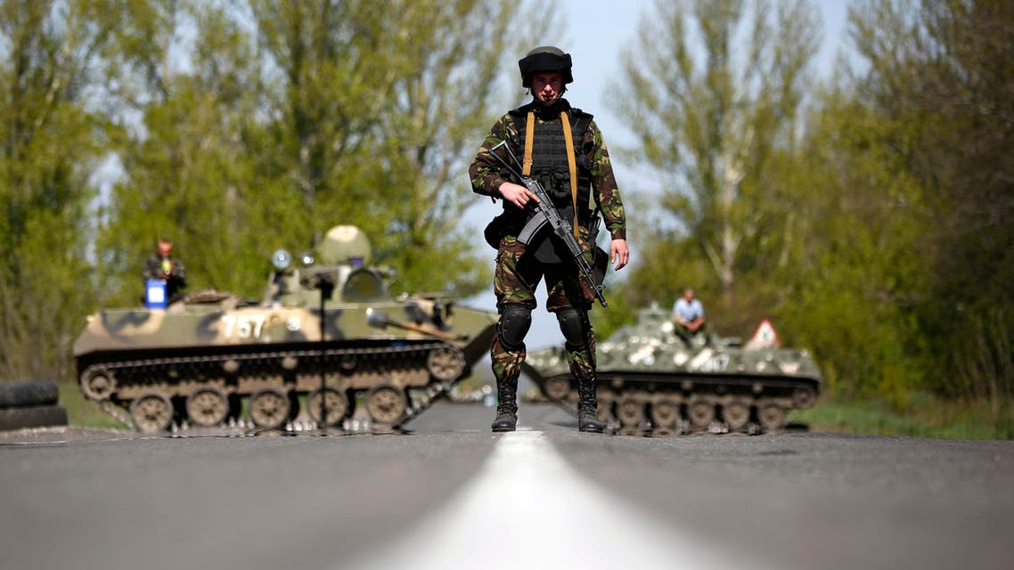 A Ukrainian soldier stands guard in front of armoured personnel carriers at a check point near the village of Malinivka, south-east of Slaviansk, in eastern Ukraine April 27, 2014. reuters
