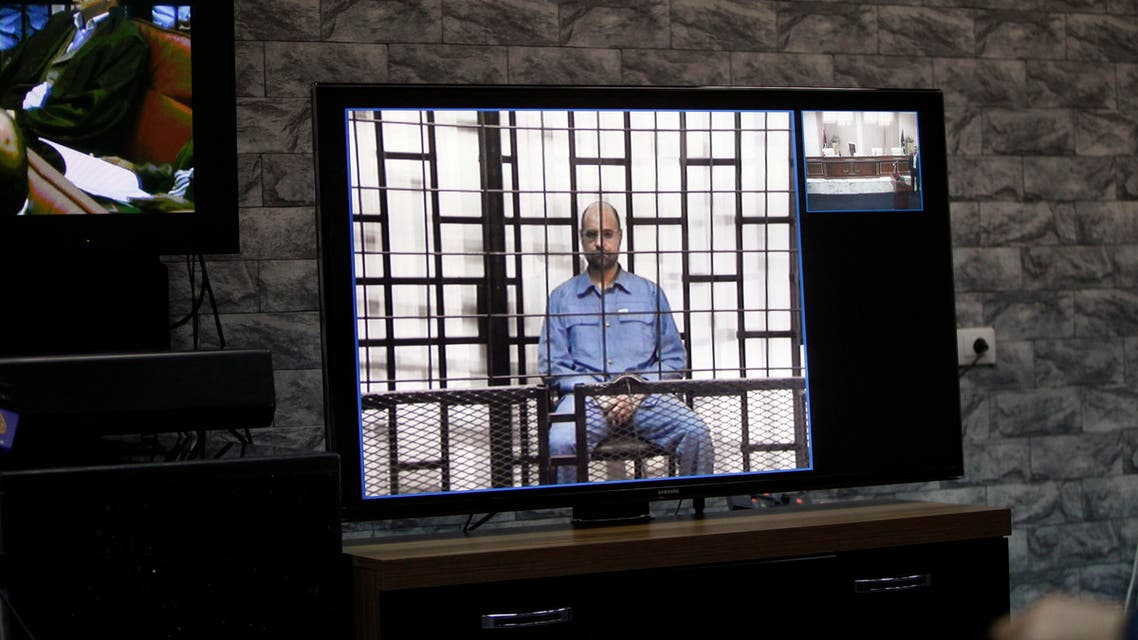 Saif al-Islam Gaddafi, son of late Libyan leader Muammar Gaddafi, is seen on a screen via video-link in a courtroom in Tripoli, May 11, 2014. (Reuters)