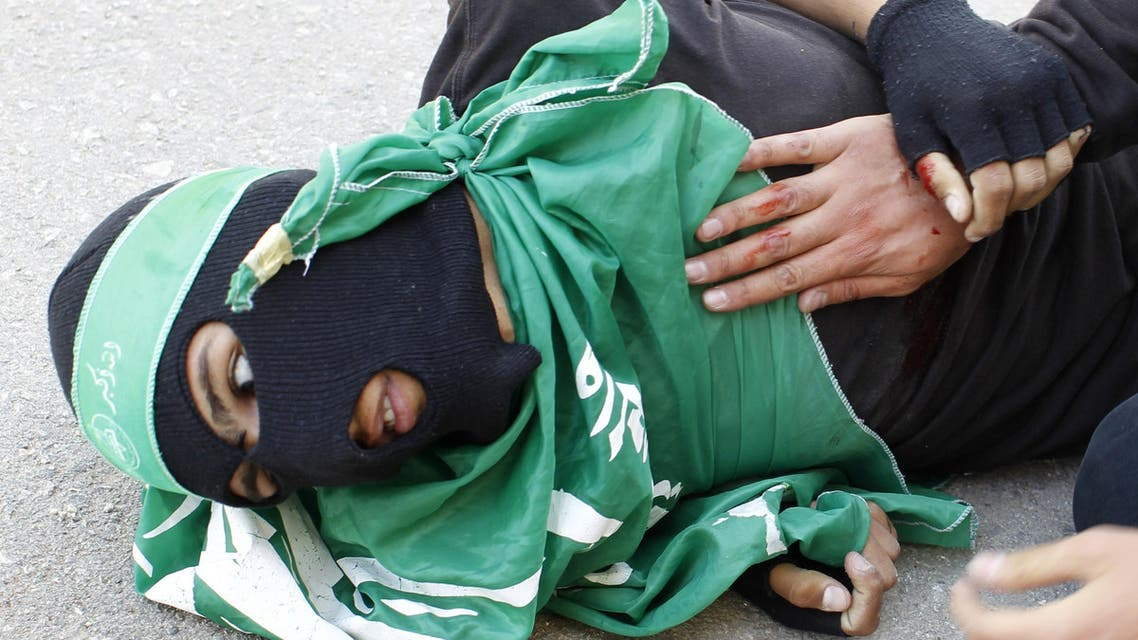 Palestinian youth Mohammed Udeh, 17,  lies on the ground after he was shot by Israeli forces. (AFP)