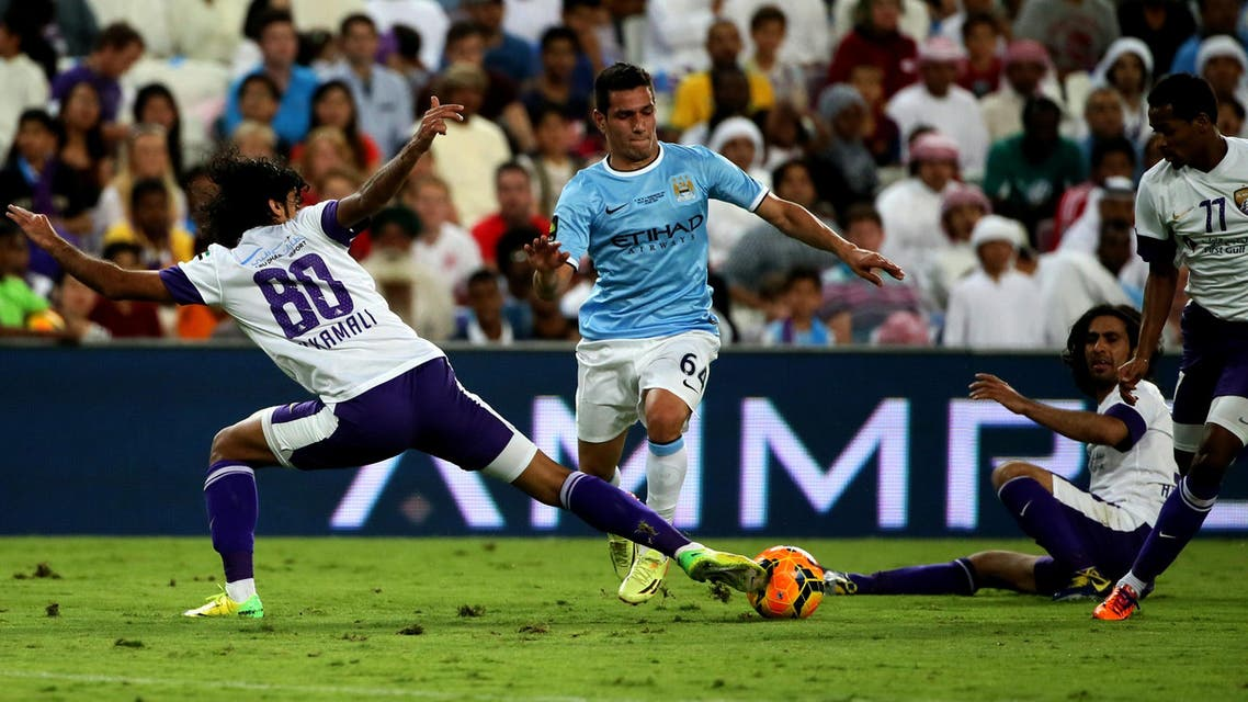Marcos Lopes (C) of newly-crowned English Premier League champions Manchester City football team dribbles the ball between UAE al-Ain players in al-Ain on May 15, 2014. (AFP
