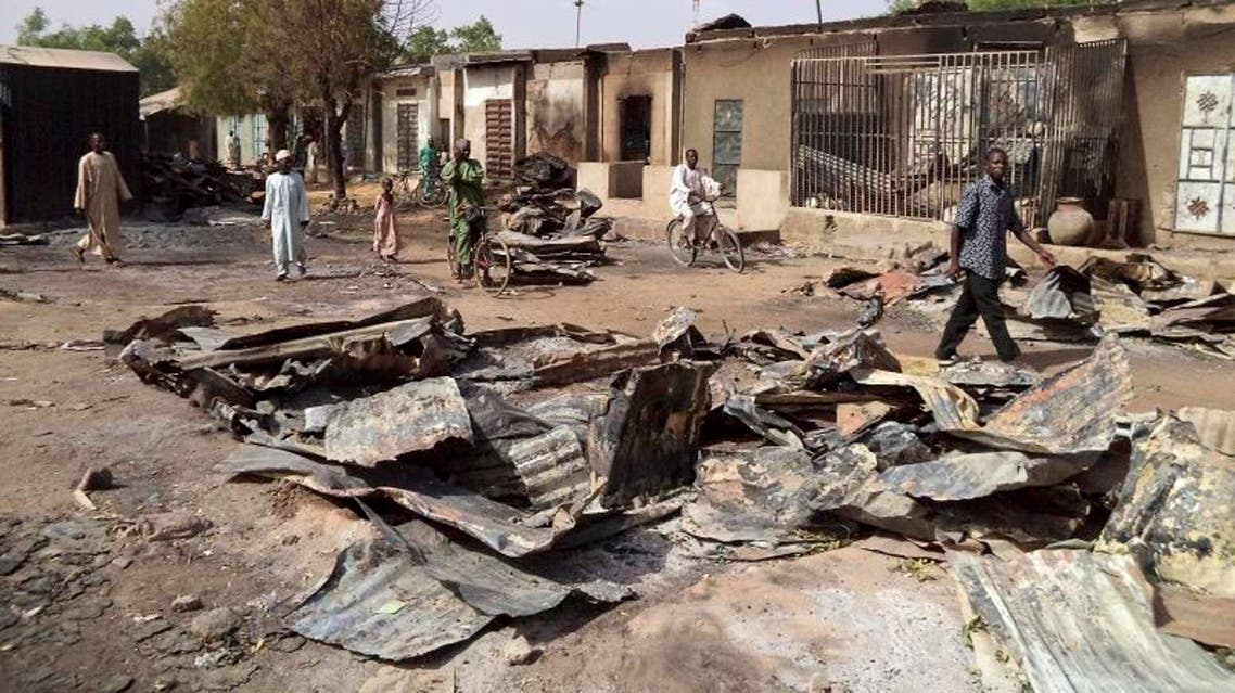People walk through the burnt ruins of Bama Market, which was destroyed by gunmen in last Thursday's attack, in Maiduguri, northeast Nigeria April 29, 2013. (Reuters)