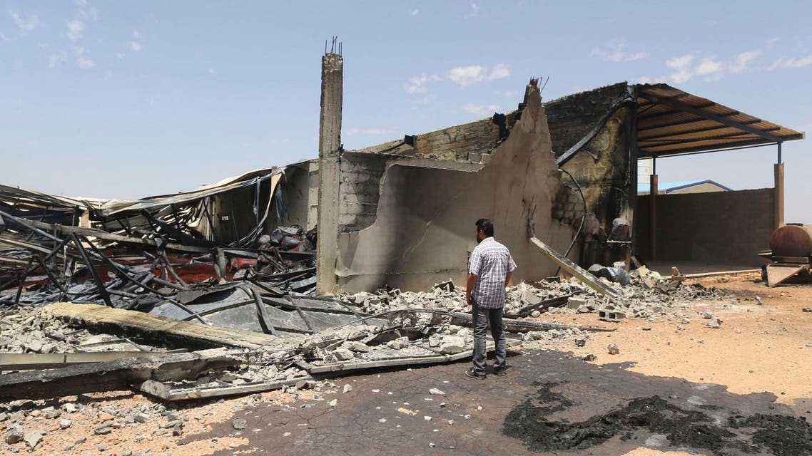 A man looks at destroyed warehouses following Friday's clashes between Libyan irregular forces and Islamist militias in the eastern city of Benghazi May 17, 2014.  (Reuters)