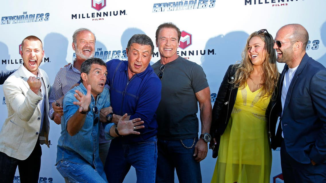 (L-R) Cast members Glen Powell, Kelsey Grammer, Antonio Banderas, Sylvester Stallone, Arnold Schwarzenegger, Ronda Rousey and Jason Statham pose during a photocall