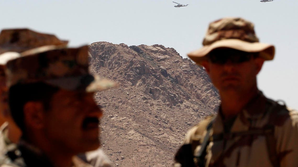 Kobra helicopters fly behind a U.S. and a Jordanian soldier during the Eager Lion military exercise near the southern town of Al Quweira, 50 km from the coastal city of Aqaba June 19, 2013.  reuters