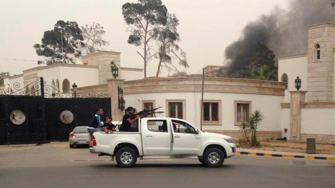 Armed men aim their weapons from a vehicle as smoke rises in the background near the General National Congress in Tripoli May 18, 2014. reuters
