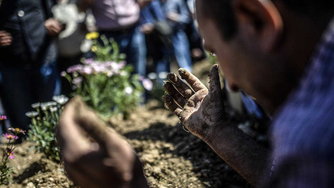 People mourn their relatives at the cemetery where some of the 301 people killed after an explosion and fire in a coal mine were buried, on May 18, 2014, at Soma in Manisa.