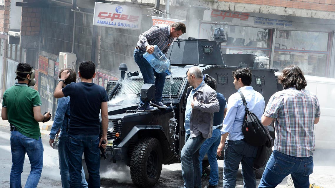 A man pours water on an armoured police vehicle after it was set on fire by fire bombs during clashes between protesters and riot police in Istanbul May 22, 2014. reuters