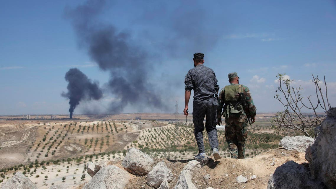 Syrian army soldiers loyal to President Bashar al-Assad walk on Hilan Hill, as smoke rises in the background, May 21, 2014. Forces loyal to Assad are moving towards Aleppo Central prison that has been sieged by rebels for over a year. (Reuters)