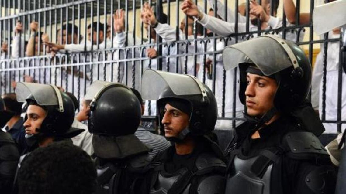 Supporters of the Muslim Brotherhood and other Islamists gesture from the defendants cage as they receive sentences ranging from death by hanging for one, life in prison for 13 and 8-15 years for the others after they were convicted of murder, rioting, and violence in a mass trial in Alexandria, Egypt, May 19, 2014. AP