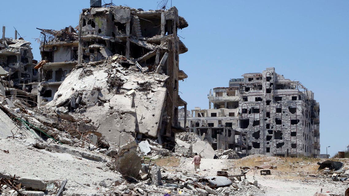 Men walk past damaged buildings as they head to inspect their homes in the Wadi Al-Sayeh district at the al-Khalidiyeh area in Homs May 14, 2014. (Reuters)