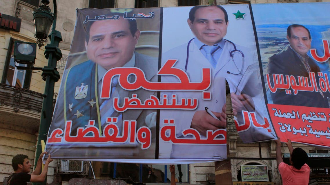 """Members of the """"April 6"""" and """"Against you"""" movement with liberal activists cut a poster of presidential candidate and former army chief Abdel Fattah al-Sisi during a protest against him and a law restricting demonstrations as well as the crackdown on activists, in downtown Cairo May 24, 2014. Egyptians vote this week in an election expected to make former army chief Abdel Fattah al-Sisi president, marking a revival of strongman rule three years after the downfall of Hosni Mubarak. REUTERS"""