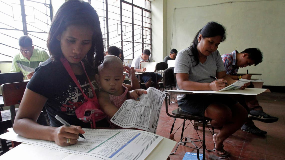 A mother with her daughter fills-up a ballot form together with other voters inside a precinct poll at a school in Manila May 13, 2013. (Reuters)
