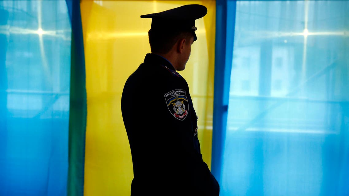 A Ukrainian policeman stands in front of a voting booth as he secures the polling station in the village of Kosmach in the Ivano-Frankivsk Oblast (province), western Ukraine May 24, 2014. (Reuters)