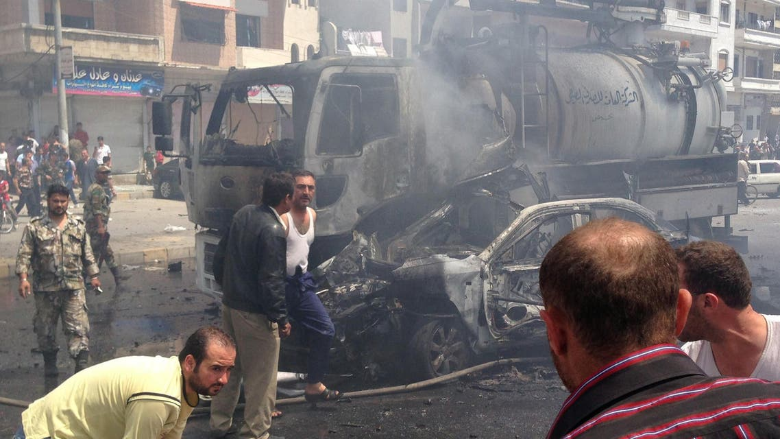 A picture taken with a smartphone on May 25, 2014, shows emergency teams gathering at the site of a car bomb attack in a regime-held area in Syria's central city of Homs, that left at least eight people dead and tens injured, according to the governor of Homs. afp