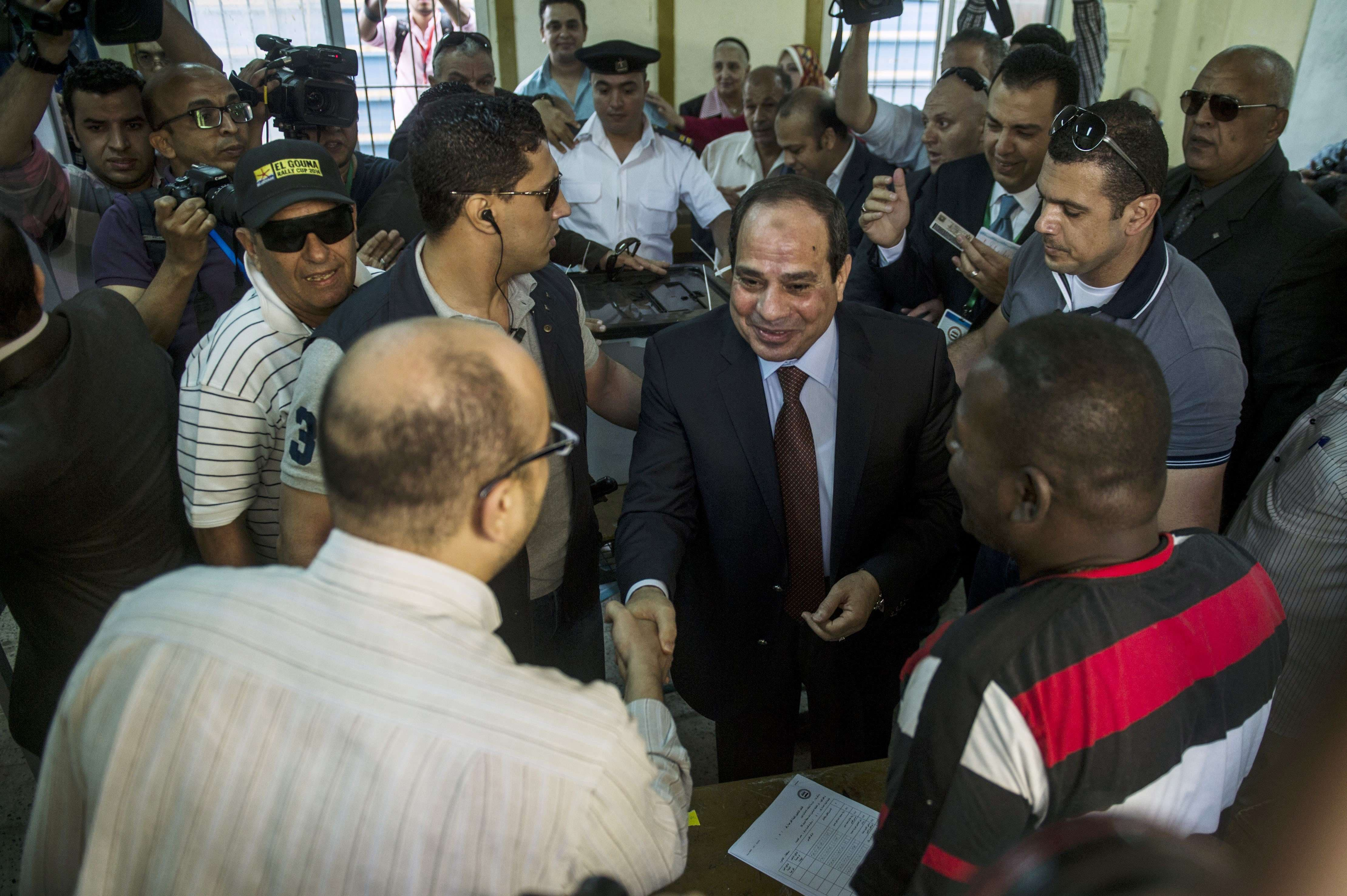 Egypt's ex-army chief and leading presidential candidate Abdel Fattah al-Sisi (C) arrives at a polling station in Heliopolis to vote in Cairo on May 26, 2014.