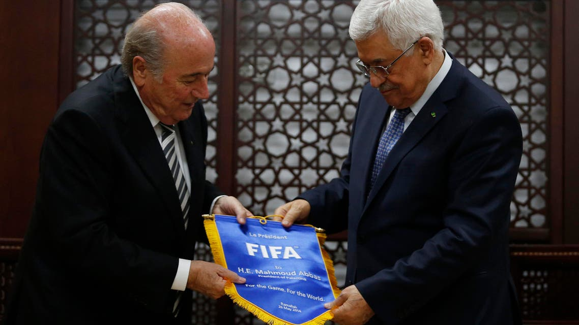 Palestinian president Mahmoud Abbas (R) receives a gift from FIFA President Sepp Blatter in the West Bank city of Ramallah May 26, 2014.