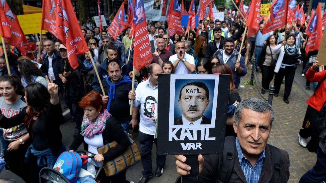 """A protester carries a poster depicting Turkish Prime Minister Tayyip Erdogan with a text reading """"Murderer"""" during a rally against Erdogan's visit in Cologne May 24, 2014."""