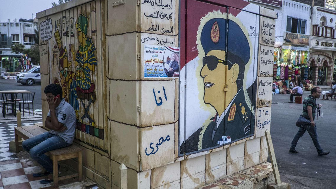 Egyptian man sitting next to graffiti of Egypt's ex-army chief and leading presidential candidate Abdel Fattah al-Sisi. (AFP)