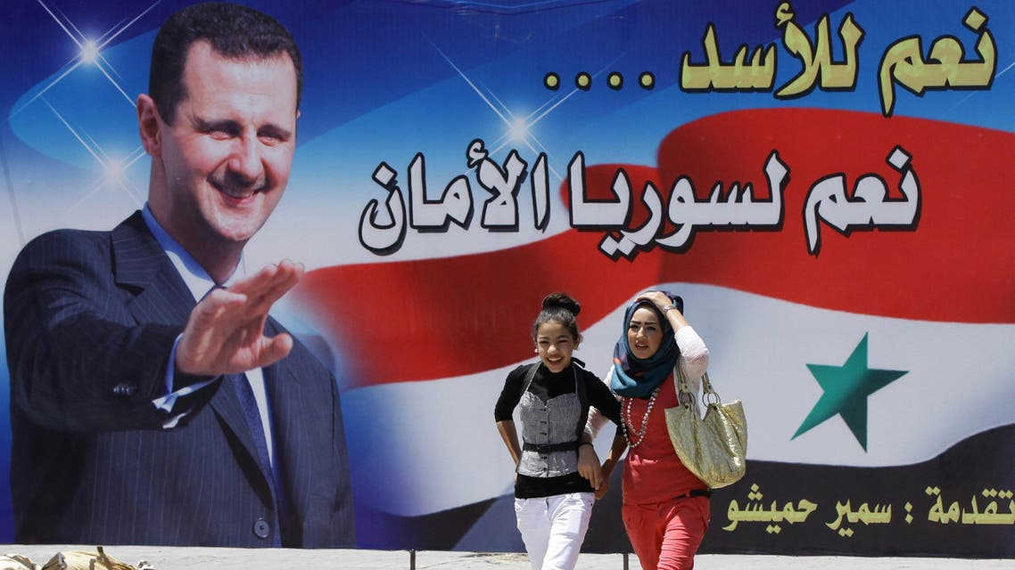 """Young Syrian women walk past a huge billboard bearing a portrait of Syrian President Bashar al-Assad, with the slogan """"Yes for Assad... Yes for a secure Syria"""" afp"""