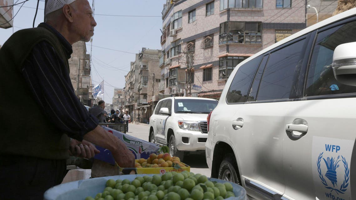 A fruit vendor stands beside passing World Food Program vehicles in eastern Ghouta of Damascus, May 24, 2014. (Reuters)