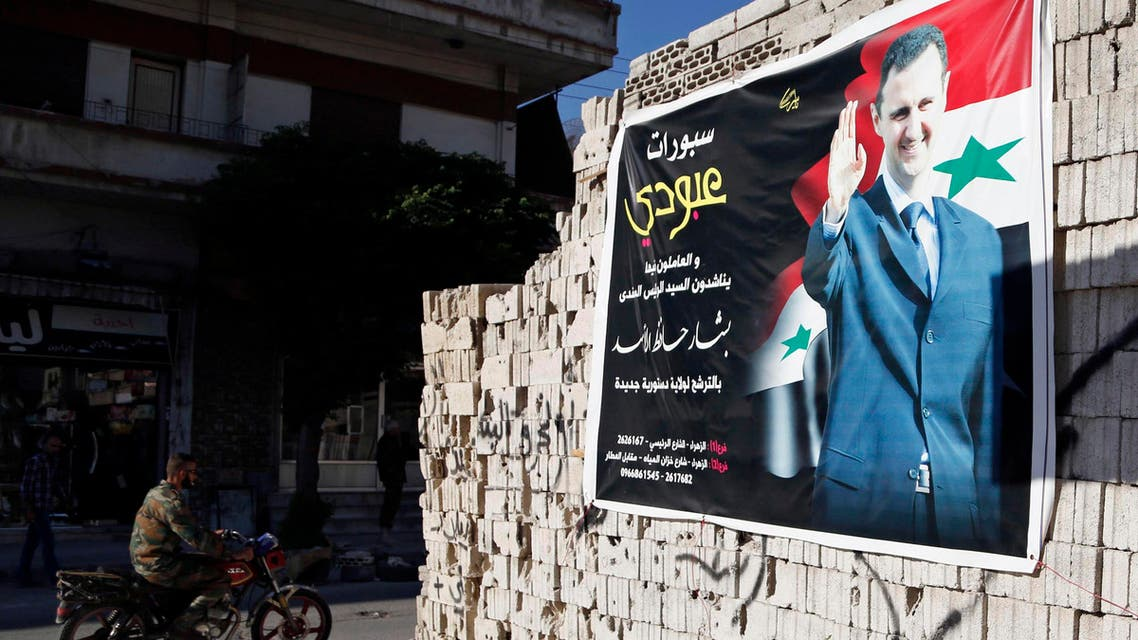 A man on a motorcycle rides past a poster depicting Syria's President Bashar al-Assad on a wall in the pro-government al-Zahraa neighbourhood in Homs May 15, 2014. reuters