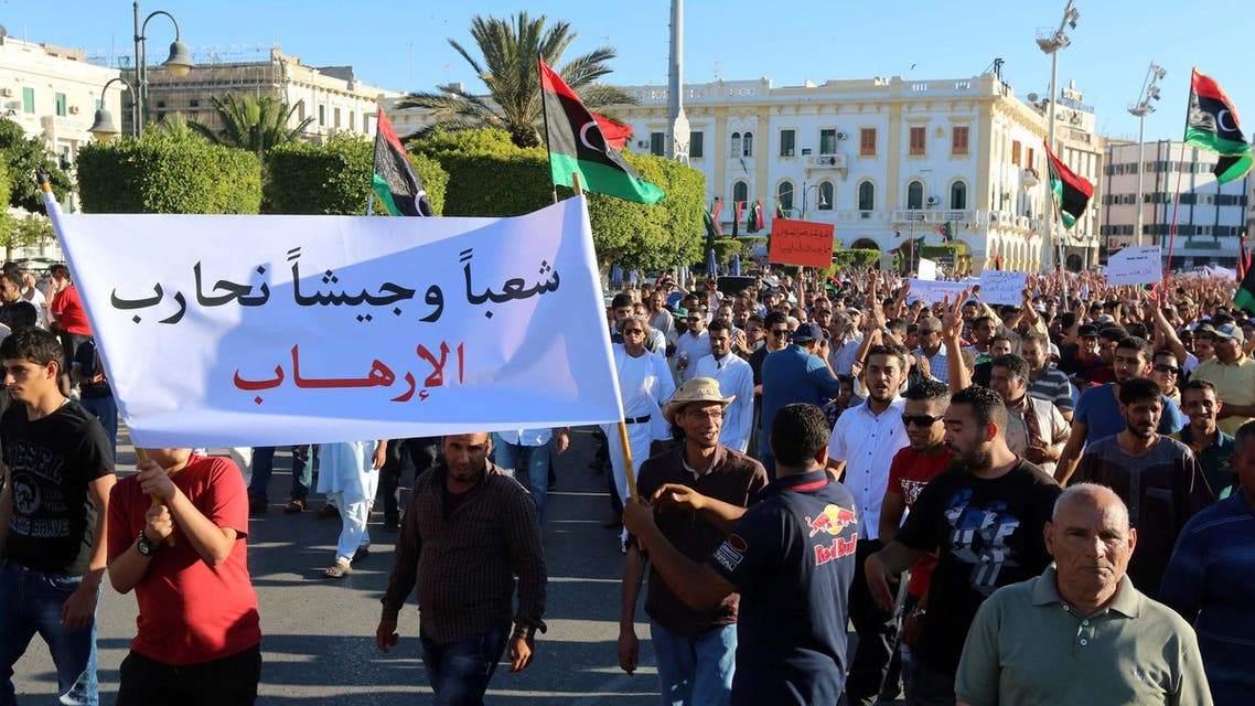 """Libyans hold placards and flags during a rally in support of a rogue former general whose forces have launched a """"dignity"""" campaign to crush jihadist militias in eastern Libya on May 30, 2014 in Tripoli. (AFP)"""
